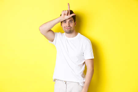 Awkward guy showing loser sign on forehead, looking sad and gloomy, standing in white t-shirt against yellow background Reklamní fotografie
