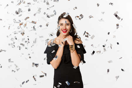 Happy woman celebrating winter holidays, smiling cheerful, partying on New Year with confetti, standing over white background