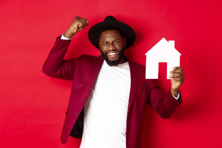 Real estate. Happy Black man celebrating, buying new house, showing paper home model and raising fist up in triumph, standing over red background