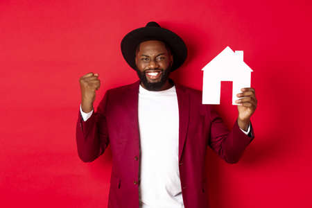 Real estate. Cheerful Black man rejoicing and showing paper home maket, standing over red background