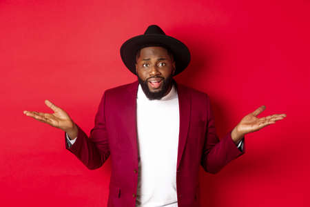 Image of confused Black man asking question, spread hands sideways and staring camera clueless, standing against red background