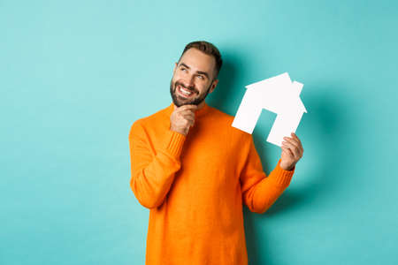 Real estate concept. Handsome adult man in orange sweater thinking about buying flat or renting, holding house maket and looking thoughtful, standing over blue background