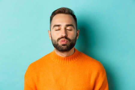 Close-up of young man in sweater pucker lips, close eyes and waiting for kiss, standing over light blue background Stock Photo