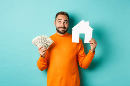 Real estate concept and mortgage concept. Handsome young man buying house, holding home maket and money, thinking and smiling, standing over light blue background