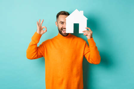 Real estate concept. Satisfied man recommending agency, showing okay sign and house maket, standing over blue background