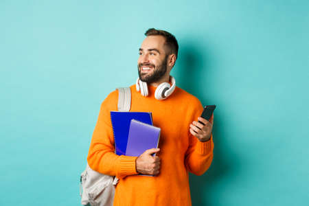 Education. Handsome male student with headphones and backpack, using mobile phone and holding notebooks, smiling happy, standing over turquoise background