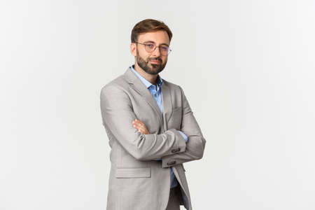 Portrait of confident businessman with beard, wearing grey suit and glasses, cross arms on chest and smiling self-assured, standing over white background
