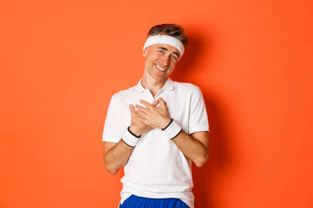 Concept of workout, sports and lifestyle. Portrait of touched and grateful adult man in sportswear, thanking and looking pleased, holding hands on heart and smiling, orange background