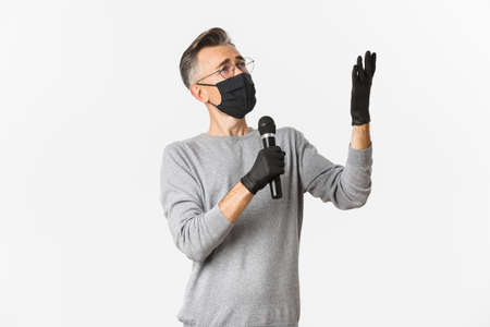 Concept of coronavirus, lifestyle and quarantine. Portrait of charismatic middle-aged man in medical mask and gloves, singing serenade in microphone, standing over white background Archivio Fotografico