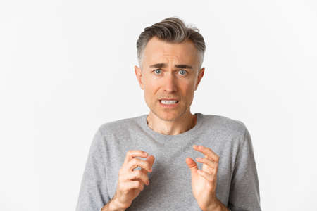 Close-up of anxious middle-aged man, looking scared and nervous, feeling guilty, standing over white background
