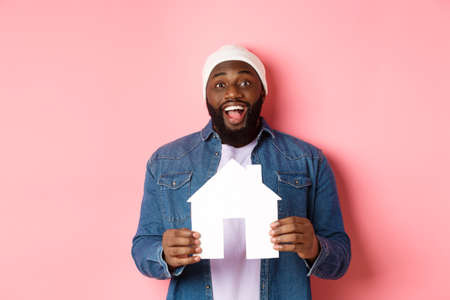 Real estate concept. Happy smiling african-american man holding house model, looking excited at camera, searching for home, standing over pink background