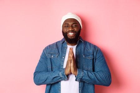 Happy smiling Black man saying thank you, holding hands in pray or namaste gesture, standing grateful against pink background Reklamní fotografie