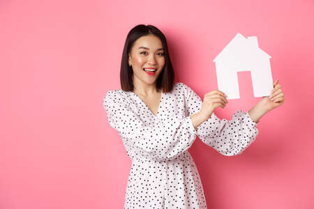 Real estate. Beautiful asian woman demonstrating paper house model, looking at camera confident, advertising home for sale, standing over pink background