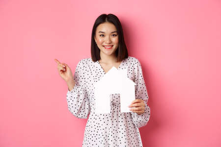 Real estate. Excited asian woman showing paper house model, pointing left at copy space, standing over pink background