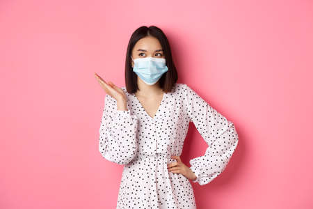 Covid-19, quarantine and lifestyle concept. Lovely asian woman in face mask raising hand, standing in dress over pink background