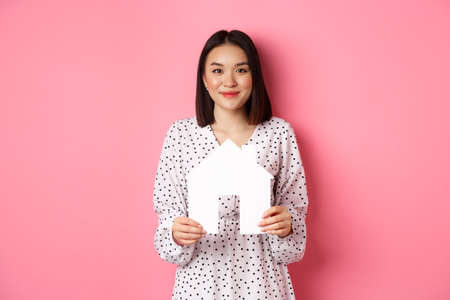 Real estate. Adult asian woman searching for home, holding house model and smiling, promo of broker company, standing over pink background