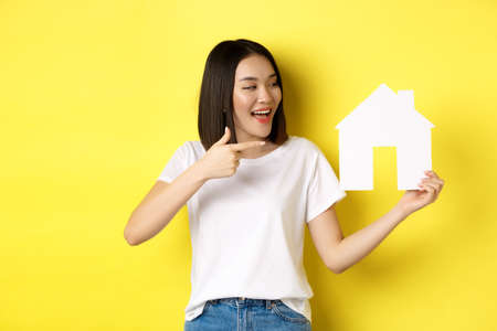 Real estate and insurance concept. Cheerful asian woman smiling, pointing and looking at paper house cutout, recommend agency logo, standing over yellow background