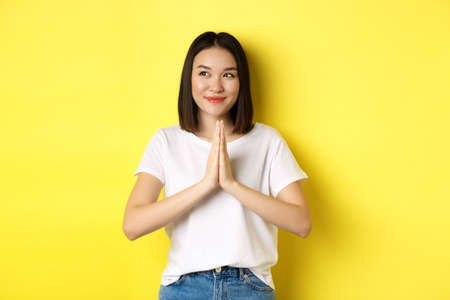 Pretty asian woman holding hands in namaste, pray gesture, looking left and smiling, say thank you, express gratitude, standing over yellow background