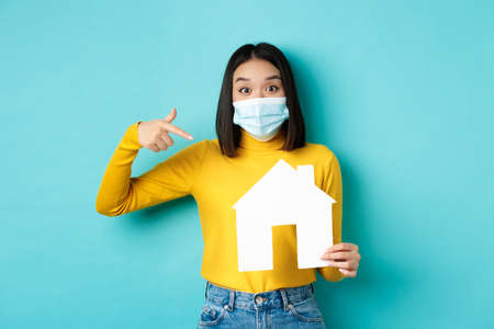 pandemic and real estate concept. Cheerful asian woman smiling in medical mask, showing paper house cutout, recommend agency for buying property, blue background
