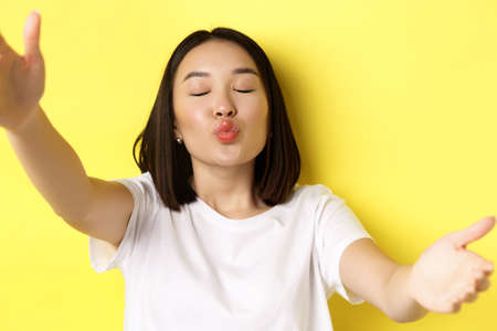 Close up of cute asian woman stretch out hands to hold smartphone camera, pucker lips and taking selfie with kissing face, standing over yellow background