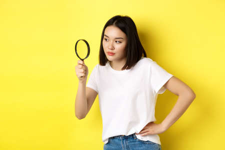 Asian woman detective looking through magnifying glass with intrigued look, found clues, standing over yellow background Foto de archivo