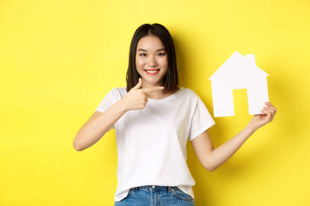 Real estate and insurance concept. Cheerful asian woman smiling, pointing at paper house cutout, recommend agency logo, standing over yellow background