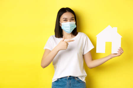 Covid-19, pandemic and real estate concept. Cheerful asian woman smiling in medical mask, showing paper house cutout, recommend agency for buying property