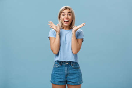 Thrilled enthusiastic happy woman in trendy t-shirt and shorts clapping hands from amazement smiling broadly and gazing with admiration at camera being surprised and joyful over blue wall