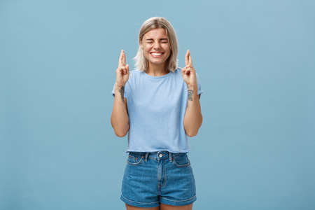 Optimistic faithful good-looking young woman with blond hair and tattoos smiling joyfully crossing fingers for good luck waiting for dream come true making wish while standing over blue background