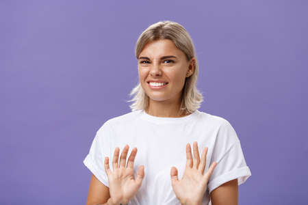 Nah no thanks. Unimpressed cute stylish woman unwilling accept offer raising palms in no rejection gesture clenching teeth while smiling with intense displeased smile frowning over purple background