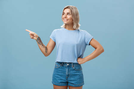 Studio shot of intrigued charming young european female with tanned skin and blond hair holding hand on waist in confident pose looking and pointing left with interest and curiosity