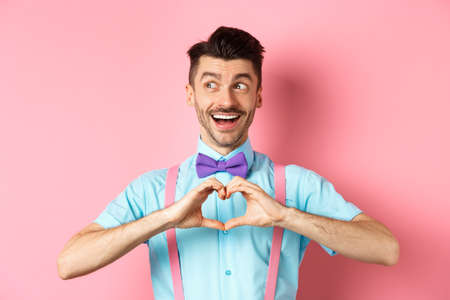 Happy Valentines day. Cheerful male model enjoying romantic date, showing heart sign, say I love you and looking left with happy smile, standing over pink background