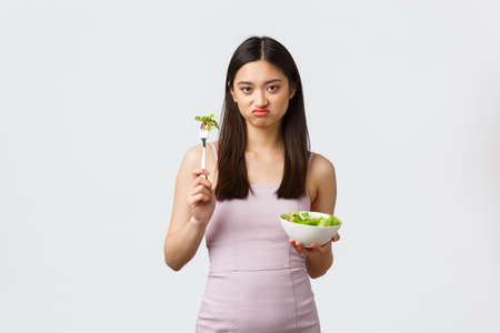 Healthy lifestyle, leisure and people emotions concept. Gloomy pouting asian girl dislike eating vegetables, holding bowl with salad, grimacing as unwilling sit on diet, white background