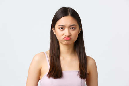 Beauty, fashion and people emotions concept. Close-up portrait of pouting upset cute asian girl grimacing, complaining over unfair situation, sulking as standing white background Standard-Bild
