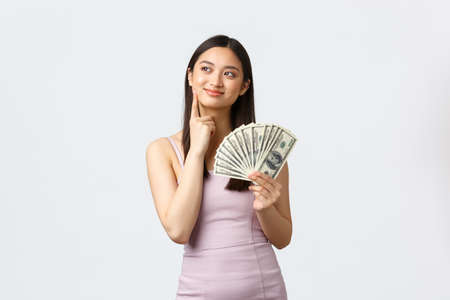 Luxury women, party and holidays concept. Dreamy rich young asian woman thinking how waste all money, got extra cash, smiling pleased imaging shopping, standing in dress over white background 스톡 콘텐츠