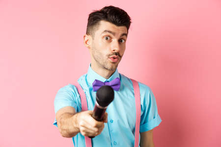 Handsome male show host stretch out hand with microphone, asking for interview or comments, standing on pink background