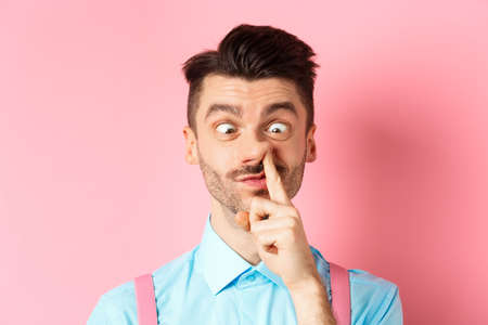 Image of funny caucasian guy picking nose and squint eyes, making dumb face, standing on pink background