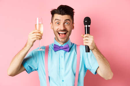 Party and festive events concept. Cheerful young male entertainer, giving speech on holiday, raising glass of chamapgne and holding microphone, making toast on wedding, pink background Stock Photo