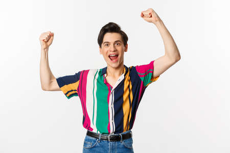 Image of happy young man triumphing of winning, celebrating victory, raising hands up in rejoice and shouting yes, standing over white background Stock Photo