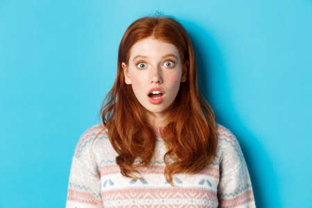 Close-up of shocked redhead girl drop jaw in awe, staring with amazement at camera, standing against blue background