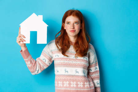 Real estate concept. Image of cute redhead girl looking curious at paper house model, thinking of buying property, looking up at copy space, blue background