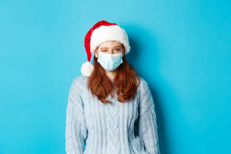 Christmas, quarantine and covid-19 concept. Cheeky redhead female model in face mask and santa hat, winking at camera, wishing merry xmas, standing over blue background