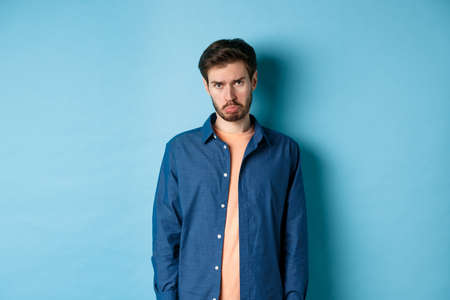 Sad and gloomy young man sulking, pulling miserable face and looking pleading at camera, standing on blue background