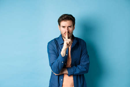 Angry man shushing, press finger to lips and frowning, tell to be quiet, show taboo gesture, standing on blue background