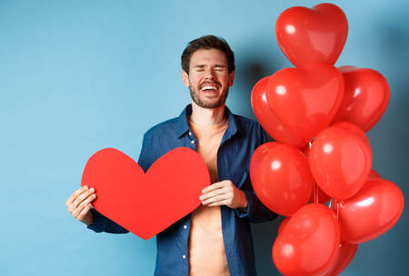 Heartbroken man crying of breakup of valentines day, holding red heart cutout and standing near romantic balloons over blue background
