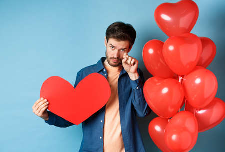 Sad and heartbroken man crying, wiping tears, standing with red heart and balloons, breakup on Valentines day, blue background