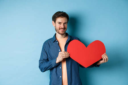 Happy man showing valentines heart and smiling, make romantic gift on lovers day, standing over blue background