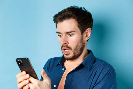 Close-up of man looking shocked and reading message on smartphone, gasping and stare startled at screen, standing on blue background