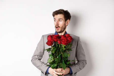 Handsome young man in suit holding red roses, looking left with surprised and startled expression, standing on Valentines day over white background