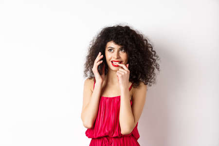 Silly fashionable woman in red dress and lips, biting fingernail duing phone call, thinking on mobile conversation, standing on white background Banque d'images